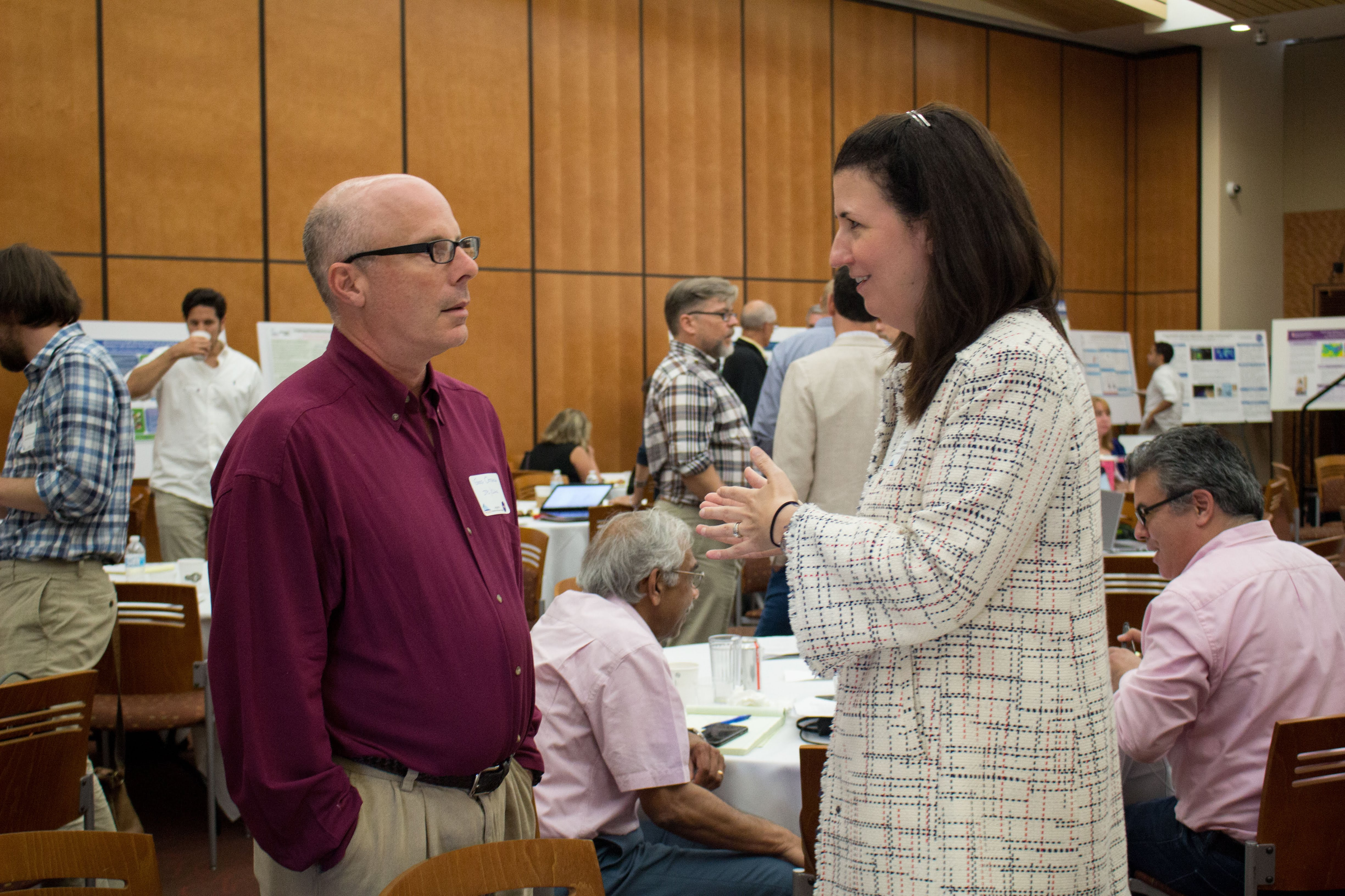 two people talking in a crowded room