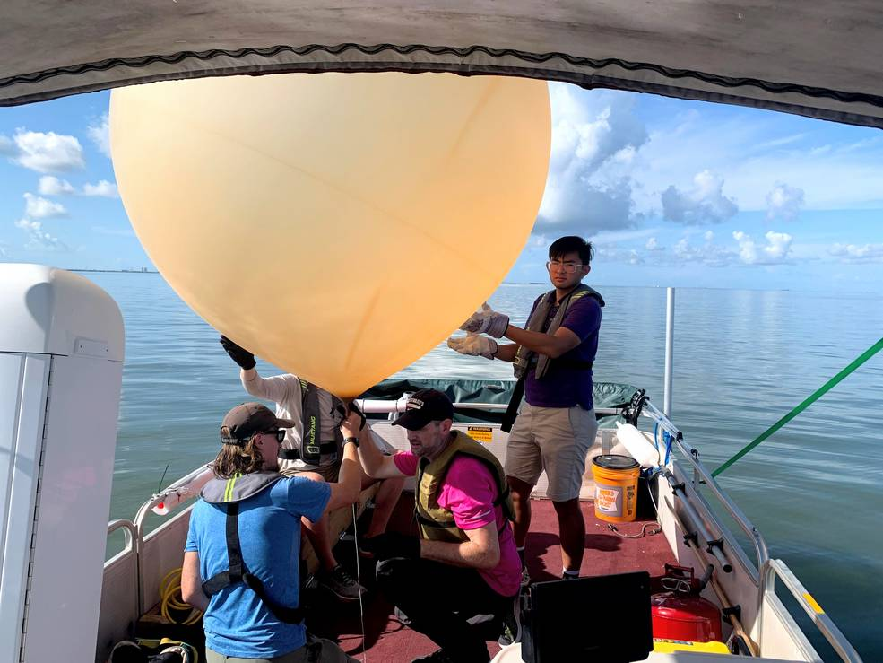 four people on boat with large research balloon