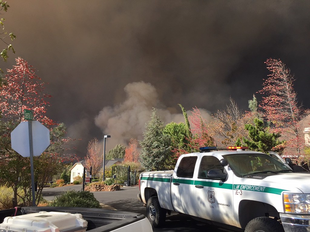truck parked in front of houses with smoke from a fire in the background
