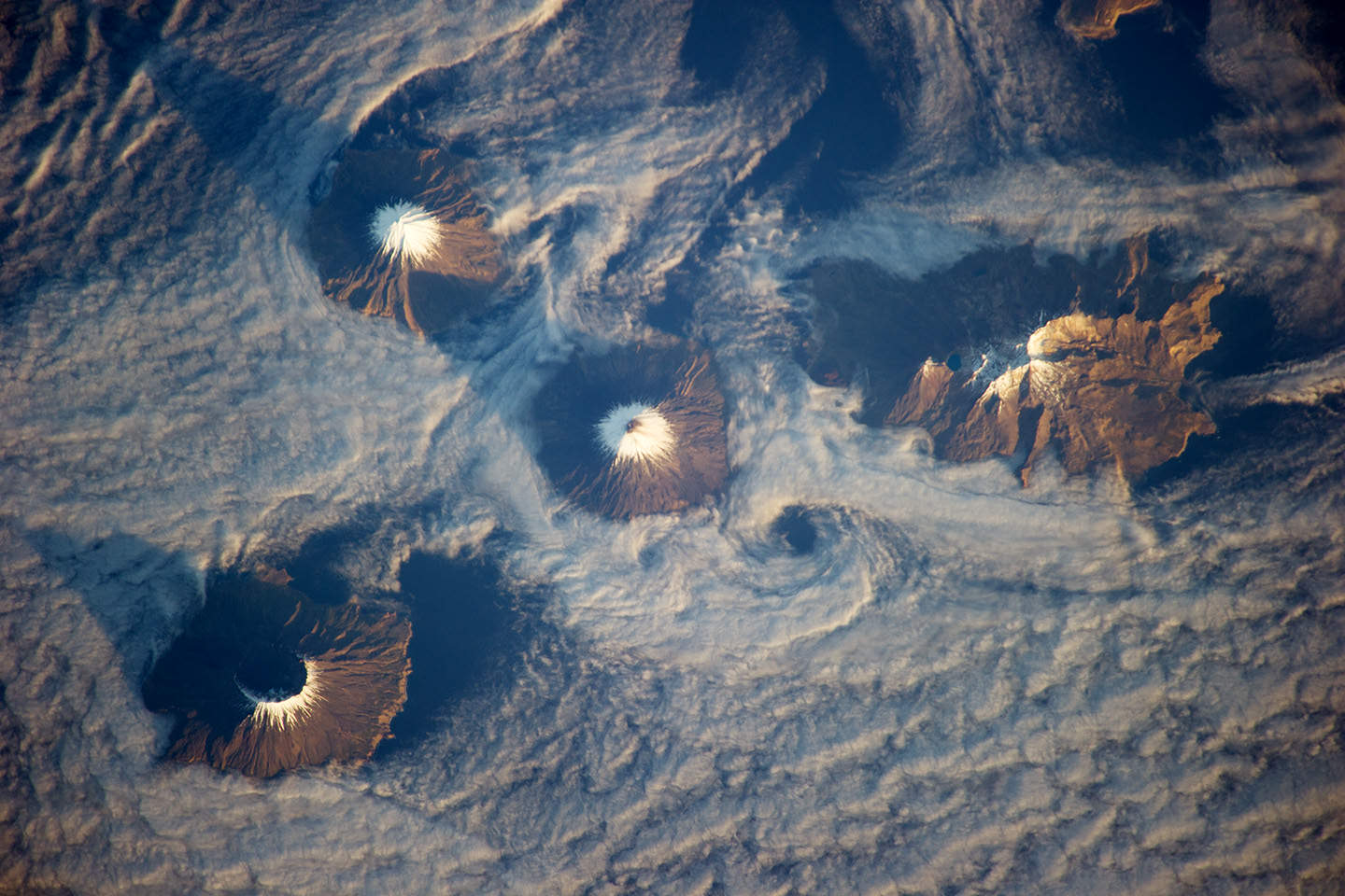 Clouds swirl around the Islands of the Four Mountains in Alaska's Aleutian chain.