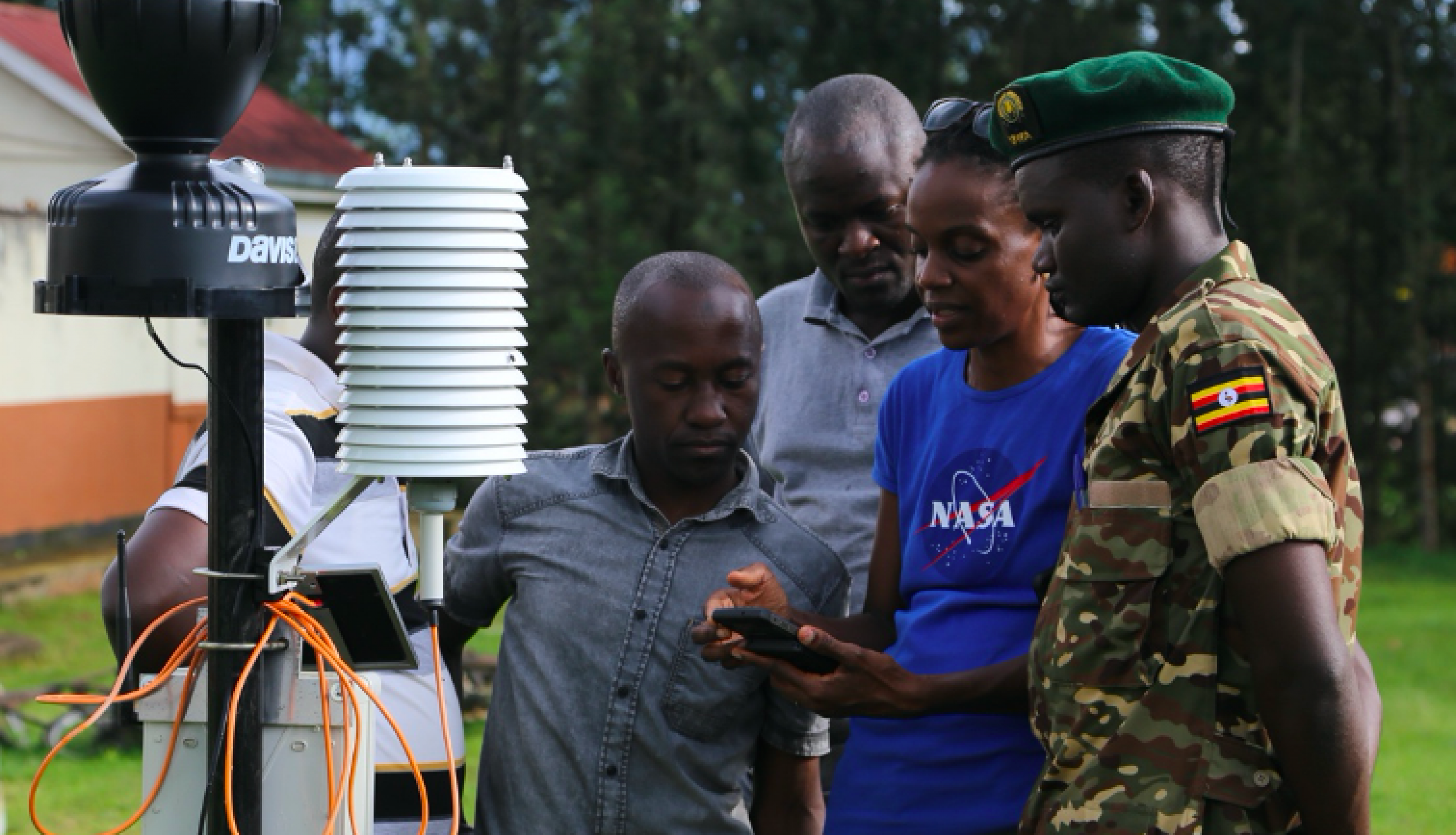 Photo of scientist showing instrument to government staff