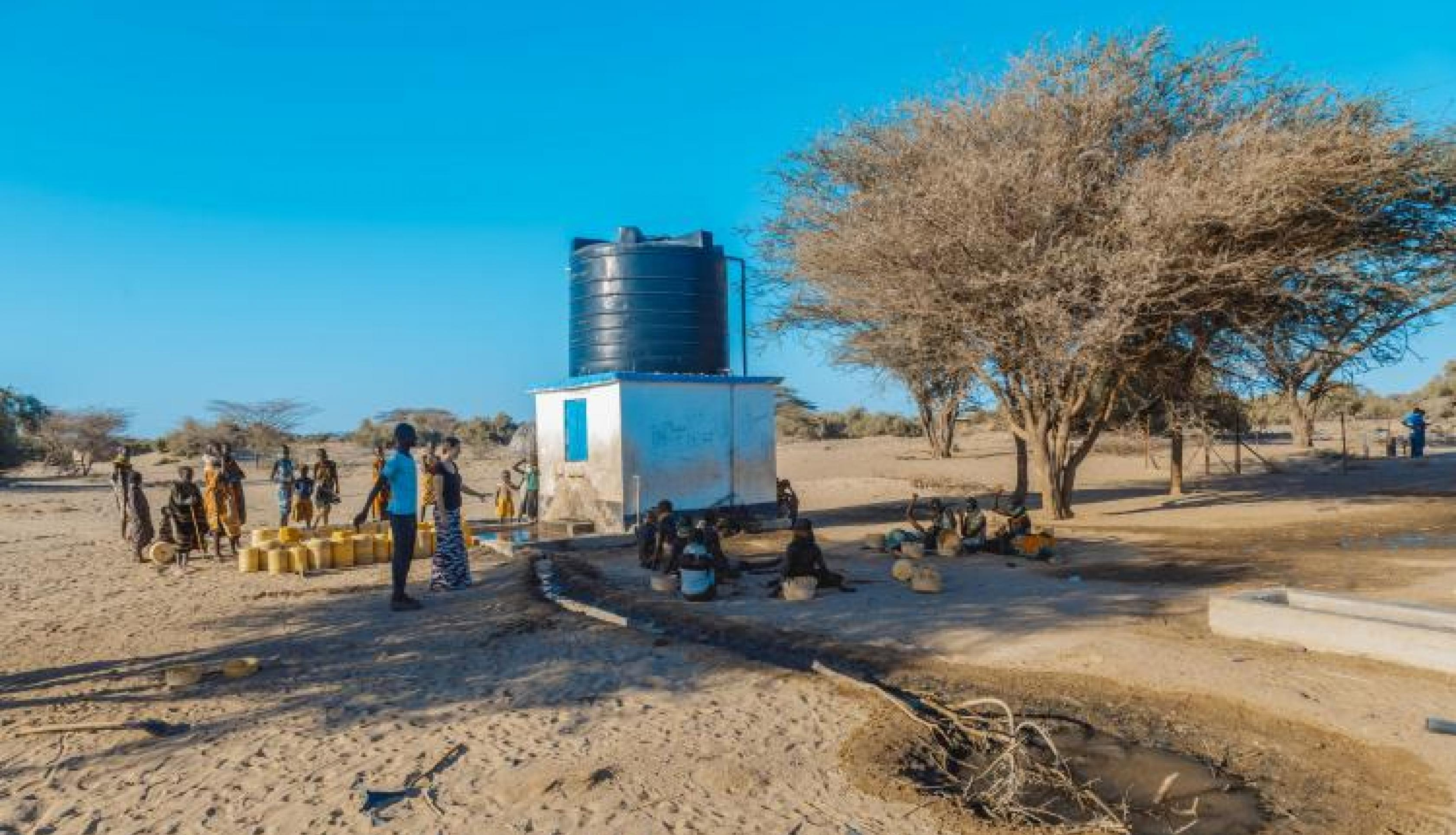 group of people near a groundwater pump