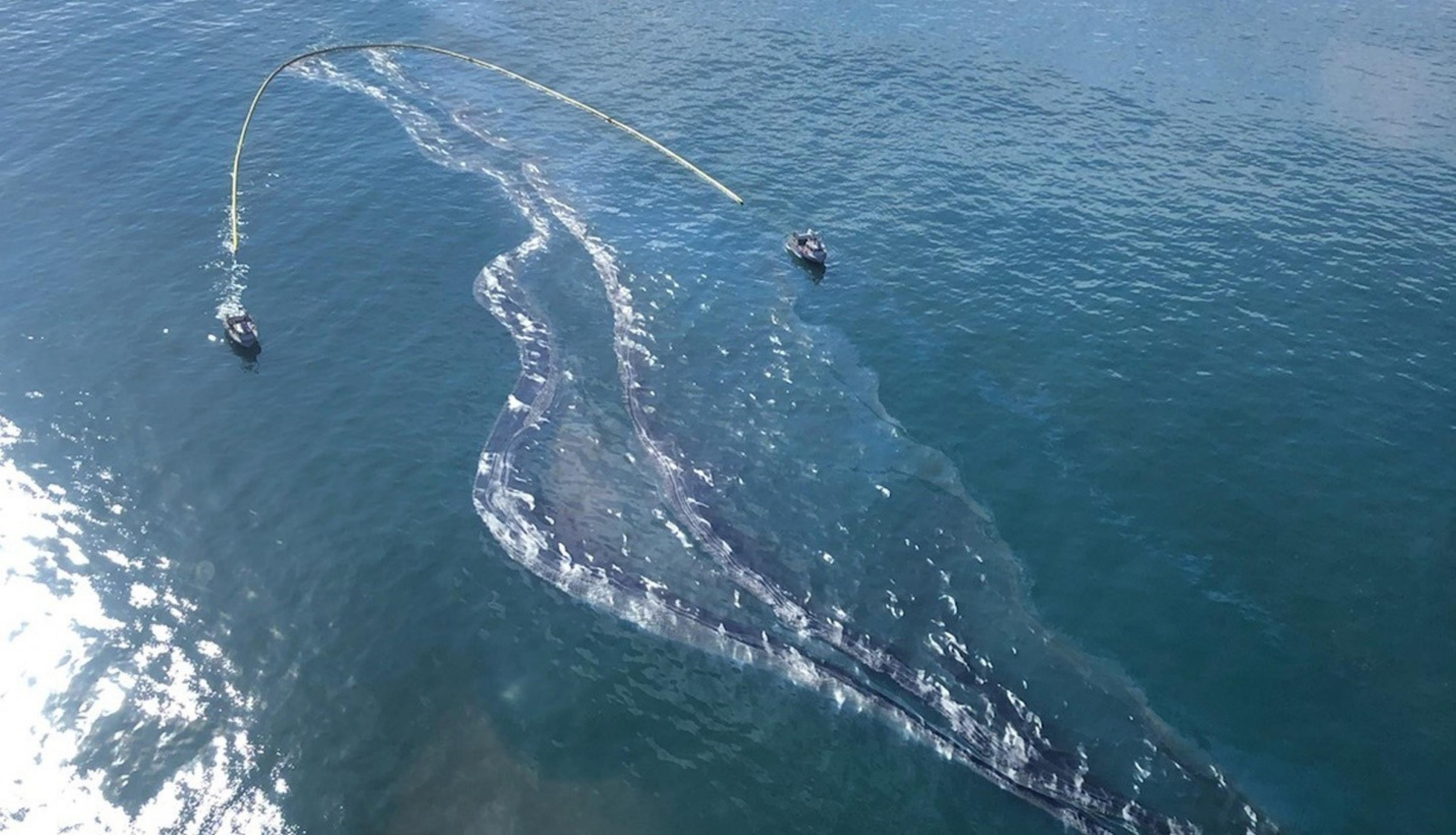 Crude oil is shown in the Pacific Ocean offshore of Orange County, California, Oct. 3, 2021. The Coast Guard said on Oct. 3 that over 5,300 feet of floating barriers, known as booms, had been deployed and that approximately 3,150 gallons of oil had been recovered from the water. Credits: U.S. Coast Guard