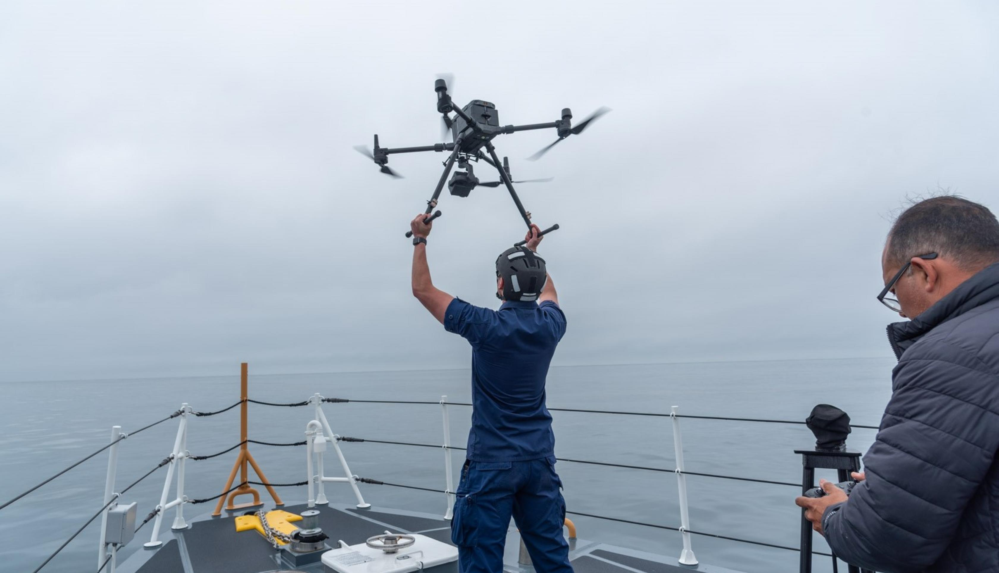 A crewmember of the Coast Guard cutter Blackfin releases a drone as part of Marine Oil Spill Thickness field campaign off the coast of Santa Barbara, CA. The drone carries a multi-spectral sensor to classify oil thickness. These data are compared with SAR imagery from NASA's aircraft UAVSAR. Oscar Garcia (right) of the Watermapping LLC controls the drone. Credits: NASA/University of Maryland/Frank Monaldo