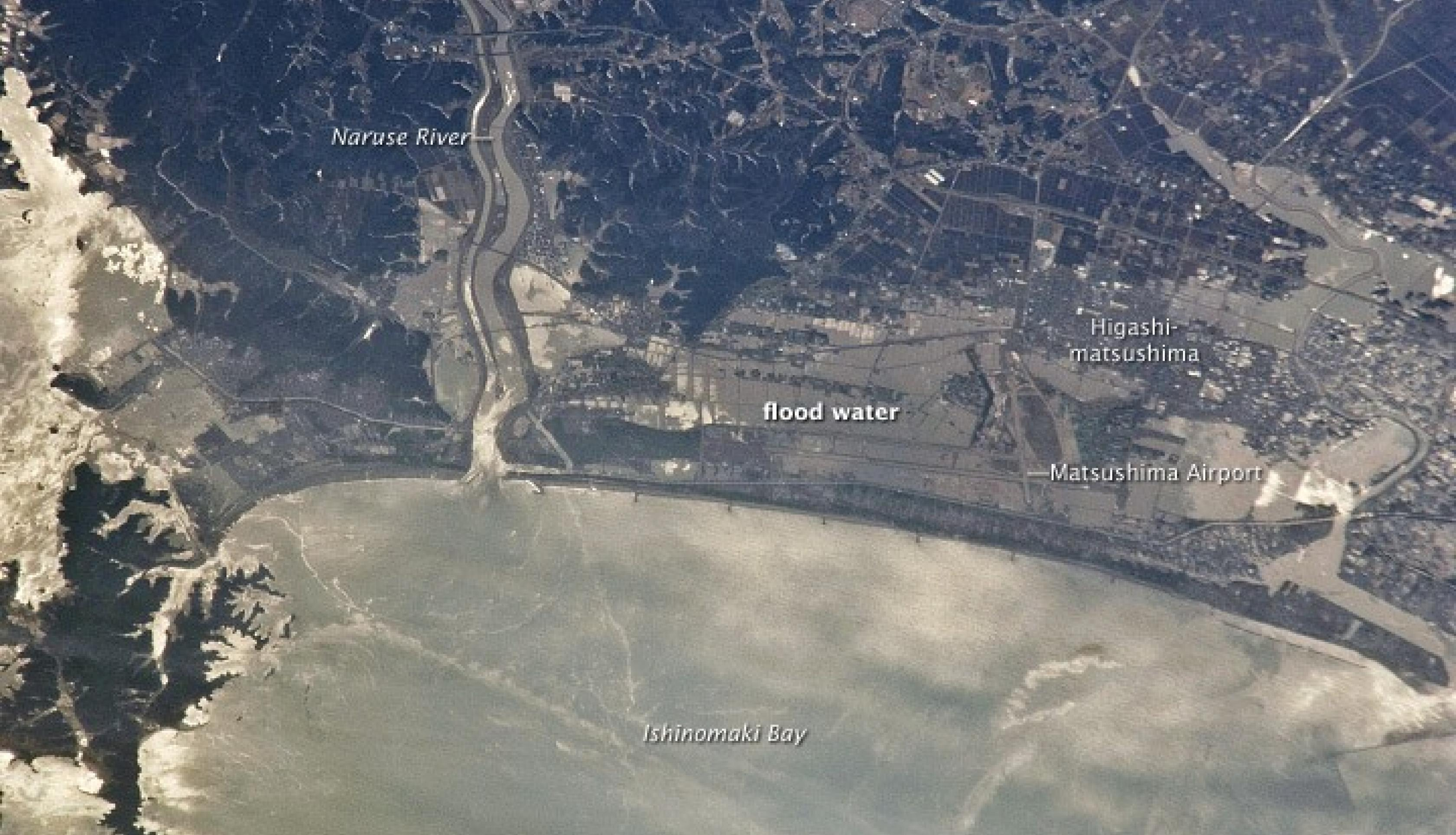 On Mar. 11, 2011, the eastern coast of Japan was shaken by the magnitude 9.0 Tohoku earthquake - one of the strongest earthquakes ever recorded. This photo, taken from the International Space Station on Mar. 13, 2011, shows the Japanese coastline north and east of Sendai following inundation by a tsunami. Sunglint indicates the widespread presence of floodwaters and indicates oils and other materials on the water surface.. Credit: NASA