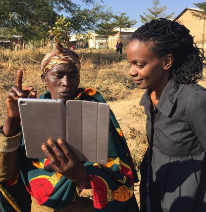 Photo of scientist showing iPad data to a Ugandan expert
