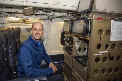 Photo of scientist Kristopher Bedka with laser