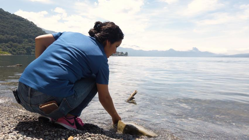 photo of a woman, Africa Flores, sampling a lake
