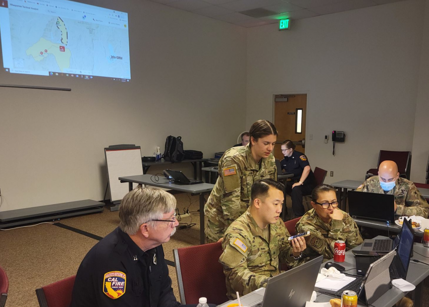 photo of people in military garb in a room looking at computers
