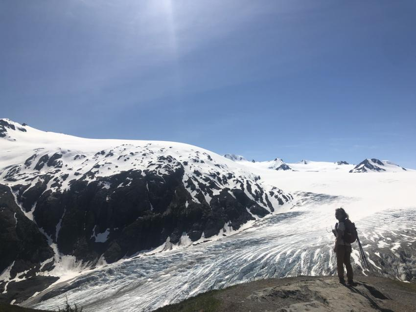 Photo of person in front of glacier