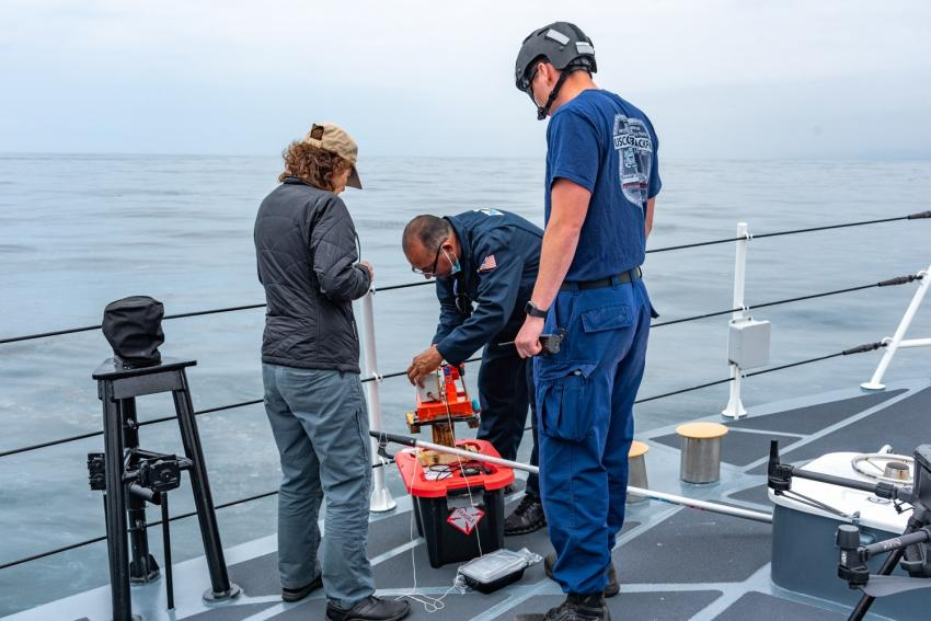 Equipment being readied to study a naturally occurring oil spill on the desk of the U.S. Coast Guard cutter Blackfin on May 10, 2021. Taking part in this MOST field test are, (l to r), the Coast Guard's Dana Tulis, Director, Incident Management and Preparedness Policy; Oscar Garcia-Pineda of Water Mapping LLC, and a Blackfin crewmember Credits: NASA/University of Maryland/Frank Monaldo