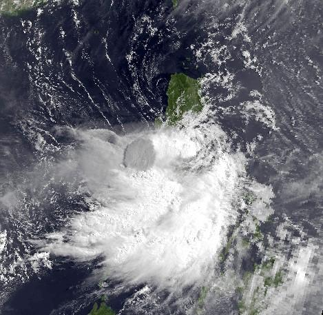 Image: Tropical Storm Yunya arrives about 5 miles away from land in this image taken by the NOAA-12 satellite on June 14, 1991. Theeruption columnfrom Mt. Pinatubo (in dark grey) can be seen through the storm's clouds. Credits: NOAA