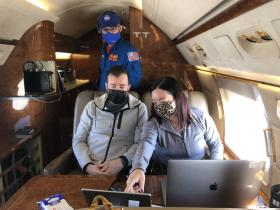 three people looking at a laptop while on a plane