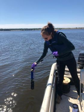 Woman on lake installing science instruments