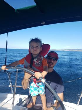 Photo of man on boat with kid and fish