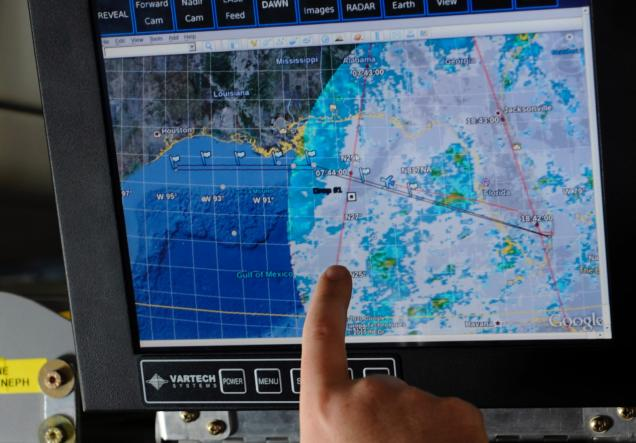 A researcher points out the trajectory of a weather pattern on a computer monitor during a flight aboard the NASA DC-8 aircraft