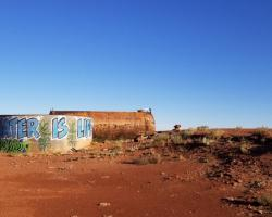 "water tank in desert with ""Water is Life"" graffiti"