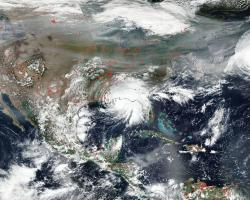 This image captured by the NOAA/NASA Suomi NPP satellite on Sep. 15, 2020 shows intense wildfires in the west (red dots) and smoke drifting across the country while several hurricanes formed – including Hurricane Sally as it stalled over Alabama (center). Credits: NASA Worldview, Earth Observing System Data and Information System